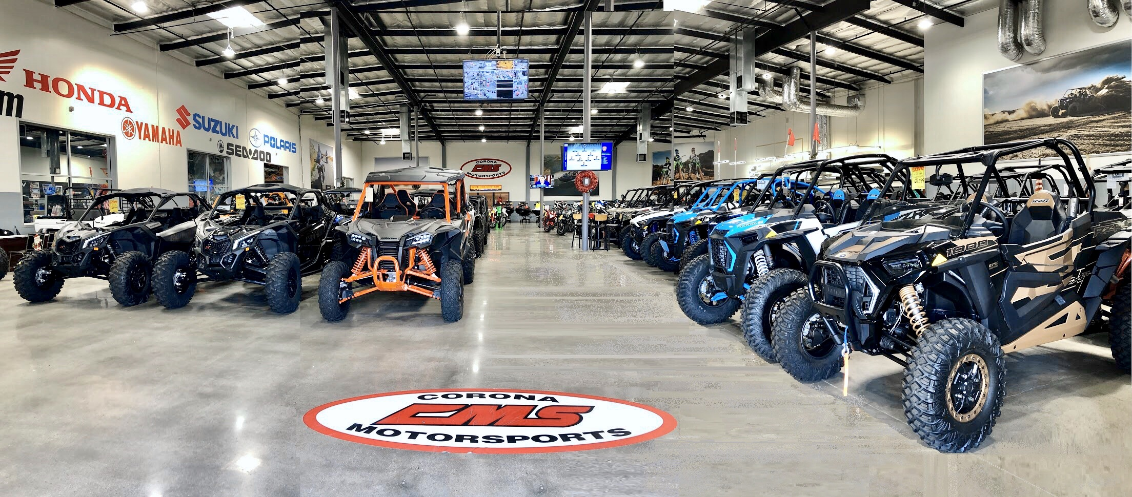 Corona Motorsports Showroom features rows of brightly colored UTVs and motorcycles.