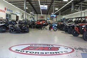 The dealership floor features the red and black Corona Motorsports logo.