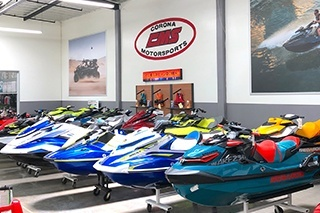 Watercraft line the showroom perimeter.